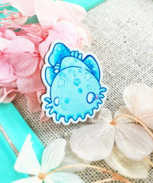 Vibrant kawaii wobbegong shark pin surrounded by dried flowers. The pin features a cartoon-like shark illustration by Evy Benita, and has a lovely and playful aesthetic.