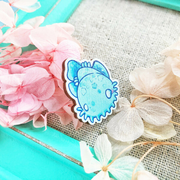 Cute and colorful Australian shark pin surrounded by dried flowers. The pin features a cartoon-like shark illustration by Evy Benita, and has a lovely and playful aesthetic. The pin is rotated slightly to the side in order to show off its thickness: roughly 2mm.