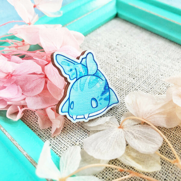 Cute Pyjama Shark wooden pin badge by Evy Benita. Here presented on a bed of dried flowers and a teal photo frame.
