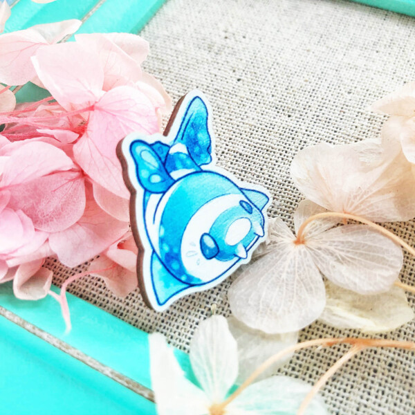 Cute chibi Bamboo Shark wooden pin badge by Evy Benita. The pin is seen from an angled view in order to show off its thickness, which is roughly 2mm.