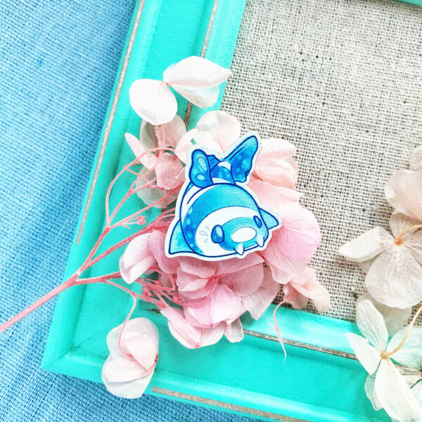 Cute chibi Bamboo Shark wooden pin badge by Evy Benita. Here presented on a bed of dried flowers on top of a teal photo frame. Super vibrant colors.
