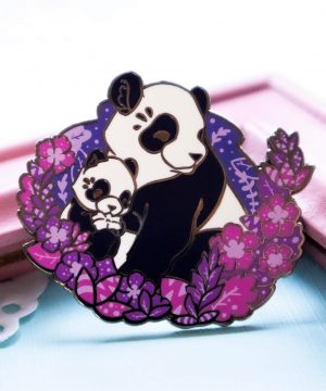 A lovely enamel pin presenting a panda mother with her cute panda cub. The two are presented in a semi-realistic art style, and sit surrounded by screen printed foliage. This panda pin is made from hard enamel and raised black nickel plated outlines.