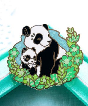 A vibrant enamel pin presenting a giant panda bear mother with her cub. The two are depicted in a semi-realistic art style, and sit surrounded by screenprinted foliage. The enamel pin is made from fresh green, blue and grey shades of hard enamel, and raised outlines in gold plated metal.