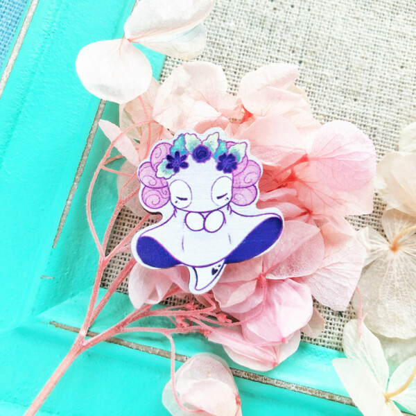 A 1-inch cartoon style wooden pin featuring Lottie the Lotl in a tranquil, soaring pose. She's wearing a ghost costume and a crown made from green leaves and dark purple flowers. Shown here presented on top of pink dryed flowers and a vibrant teal photo frame.
