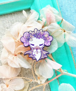 A kawaii style wooden pin badge featuring Lottie the Lotl in an autumnal setting. Lottie is wearing an earth brown cape and a crown of autumn leaves and flowers. She is holding and smelling a flower.