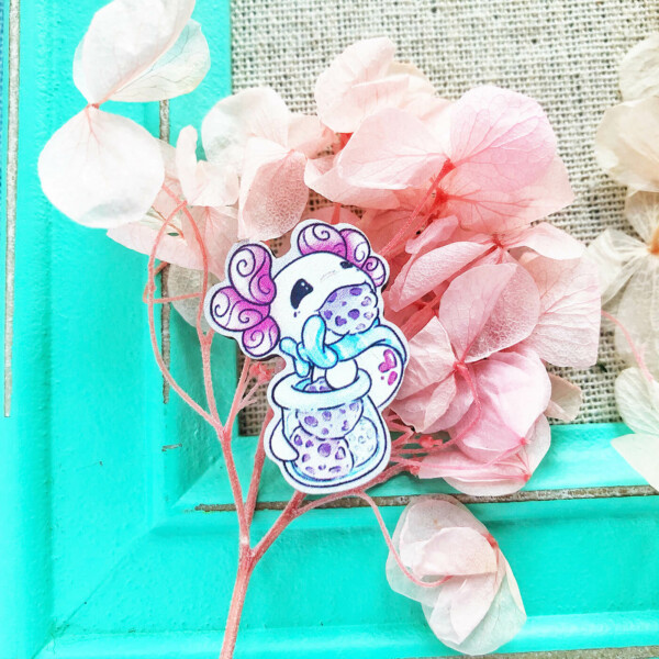 A 1-inch cartoon style wooden pin featuring Lottie the Lotl clinging onto a cookie jar. She's got one hand in the jar, and one giant cookie sticking out of her mouth. Illustrated by Evy Benita.