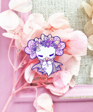 A wooden pin of a kawaii axolotl dressed up in a cape and a crown of fall foliage. Illustrated by Evy Benita