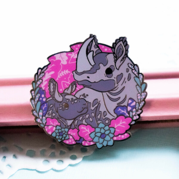A lovely enamel pin presenting a black rhino mother with her baby, The two are presented in a semi-realistic art style, and stand surrounded by screenprinted foliage. The enamel pin is made from hard enamel and raised black nickel plated outlines.