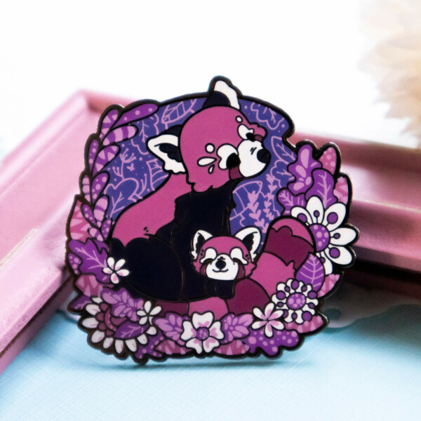 A sweet and playful, highly detailed enamel pin depicting a red panda mother circling her tail protectively around her cub. The two red pandas are depicted in a semi-realistic illustrated style, surrounded by pink and purple foliage with screenprinted details.