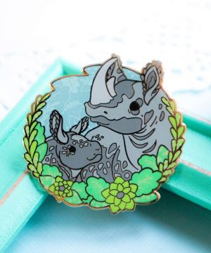 A vibrant enamel pin presenting a black rhino mother with her baby. The two are depicted in a semi-realistic art style, and stand surrounded by screenprinted foliage. The enamel pin is made from fresh green, blue and grey shades of hard enamel, and raised outlines in gold plated metal.
