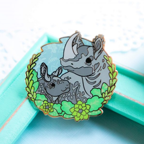 One of my charity enamel pins: a vibrant enamel pin presenting a black rhino mother with her baby. The two are depicted in a semi-realistic art style, and stand surrounded by screenprinted foliage. The enamel pin is made from fresh green, blue and grey shades of hard enamel, and raised outlines in gold plated metal.