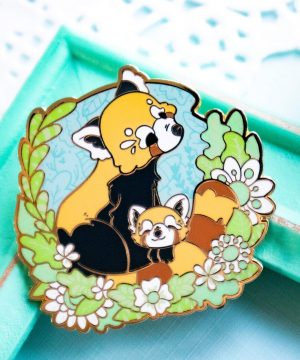 A highly detailed enamel pin featuring a red panda mother circling her tail protectively around her cub. The two red pandas are depicted in a semi-realistic illustrated style, surrounded by green foliage and backed by a blue sky. The enamel pin features screenprinted foliage details, and is completed raised outlines in gold plated metal.