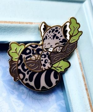 An adorable clouded leopard enamel pin by Evy Benita. The pin shows a clouded leopard sleeping with its paws wrapped around a tree branch. Green leaves decorate the outer edges of the composition at random, adding a pop of color to the design.