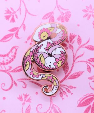 A tranquil hard enamel pin decorated with floral details. The sea snake pin badge is plated with rose gold, and features pink, yellow and white colors in a semi-realistic art style. The photo shows minor chips in the enamel on the snake's head, which is why these pins are reduced in price.