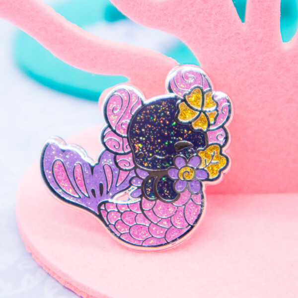Luna the Merlotl: an axolotl-inspired mermaid pin, made with glitter-filled enamel and shiny silver plating. By Evy Benita.