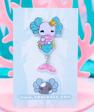 A kawaii axolotl-inspired mermaid enamel pin made from sparkly glitter, silver plating and hard enamel. The enamel pin has a small tail-fin charm dangling from it.