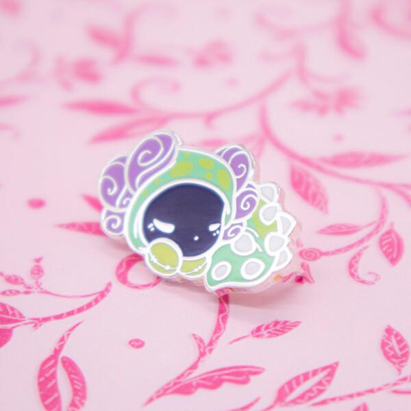 """A sleepy and utterly adorable axolotl enamel pin dressed up in an """"Ankylosaur"""" dinosaur onesie."""