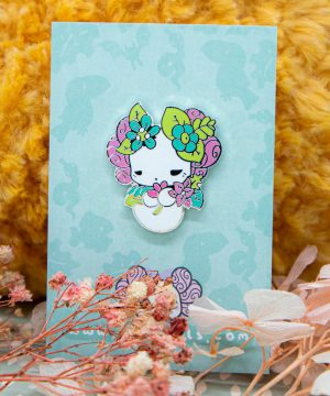 A hard enamel pin featuring a kawaii axolotl, decorated by rainforest flowers and hovering peacefully. A super cute gift for friends and kawaii fans!