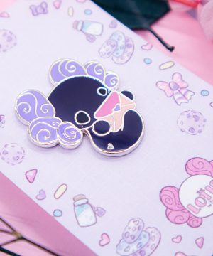 A cute enamel pin showing a chibi style axolotl holding an envelope. Presented on a cute pastel backing card.
