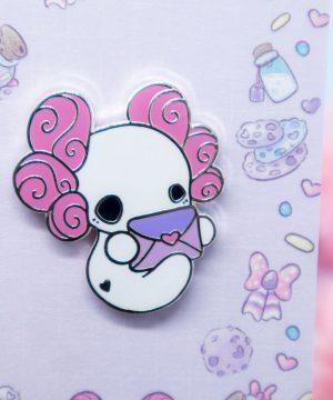 A cute enamel pin showing a chibi style axolotl holding an envelope.