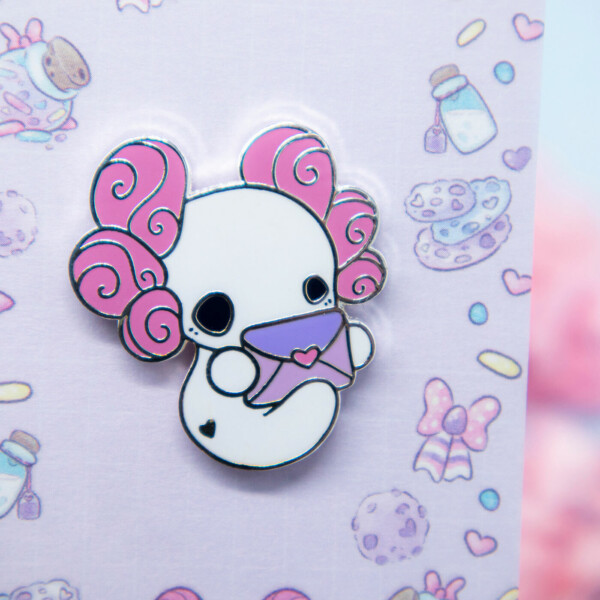 A cute enamel pin showing a chibi style axolotl holding an envelope.