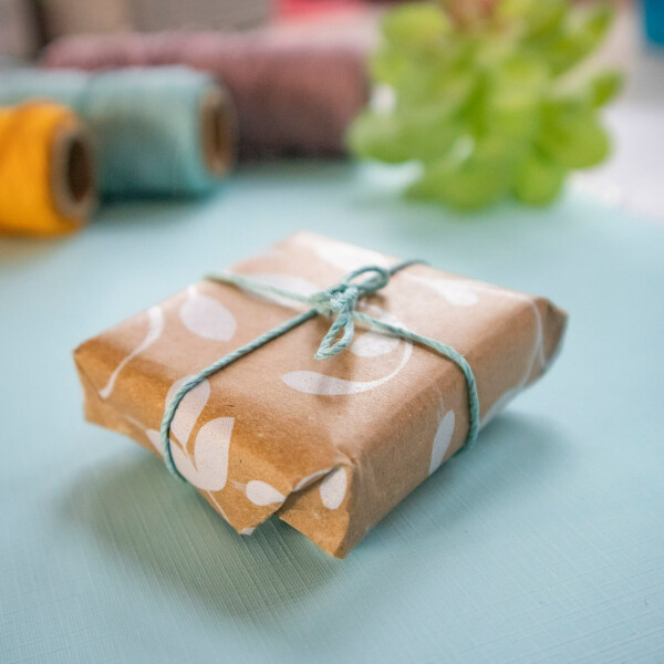 Shows a box wrapped with eco friendly gift wrapping paper. The gift wrap is made from thick kraft paper and decorated with white, elegant swirls. The gift wrap is secured with eco friendly blue hemp string, and a white paper gift tag is attached. The blue tag can have a gift message printed to it, but is shown without a message.