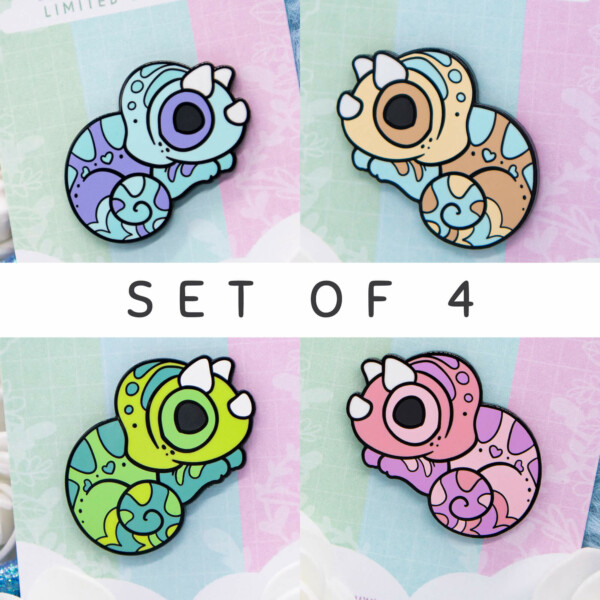A set of four cartoon-style chibi chameleon enamel pins with black nickel outlines. The outlines are made from raised metal, however they're rather indistinguishable from the enamel.