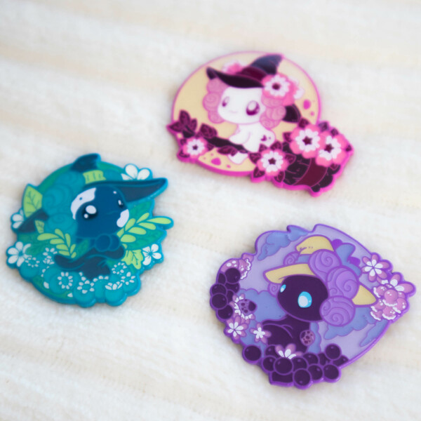 """Three colorful axolotl enamel pins illustrated in a cartoony """"chibi"""" style. These characters are part of Evy Benita's character franchise: The Lotls. Each pin is decorated with organic floral elements, and comes with color matched rubber heard backers. These pins are coated with epoxy, which means the raised outlines have been covered by a flat overarching layer."""