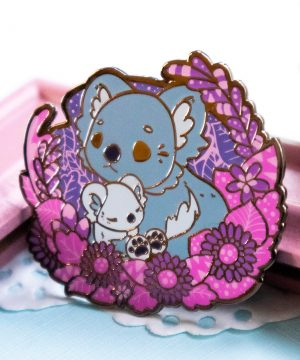 A lovely koala enamel pin depicting mother with her koala cub. The two are presented in a semi-realistic art style, and stand surrounded by screenprinted foliage. The enamel pin is made from hard enamel and raised black nickel plated outlines.