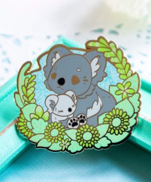 A vibrant wildlife-inspired koala enamel pin depicting mother with her koala cub. The two are presented in a semi-realistic art style, and stand surrounded by screenprinted foliage. The enamel pin is made from hard enamel and raised outlines in gold plated metal.