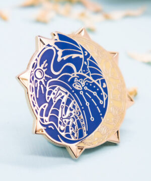 A hard enamel pin featuring a stylized (not cartoon style) deep-sea anglerfish. The enamel pin is framed by raised outlines plated with gold. The anglerfish pin has two colors: a deep blue and a warm yet subtle yellow. The color palette is inspired by early star charts and astronomy.