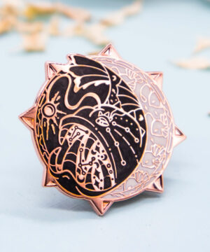 A hard enamel pin featuring a stylized (not cartoon style) deep-sea anglerfish. The enamel pin is framed by raised outlines plated with rose gold. The anglerfish pin has two colors: black and white, giving it a strong contrast. Combined with the rose gold and pearlescent effect, this pin has a lovely vintage aesthetic to it.