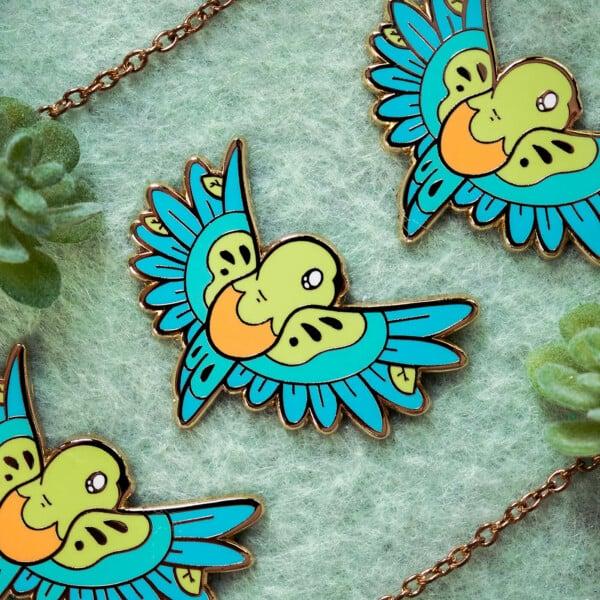 Colorful orange-bellied parrot enamel pin bird design by Evy Benita