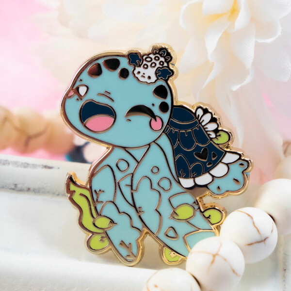 Cute enamel pin design showing a cartoon-style leatherback sea turtle playing with a nudibranch.