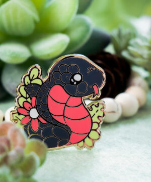 Cute red-bellied black snake enamel pin design by Evy Benita