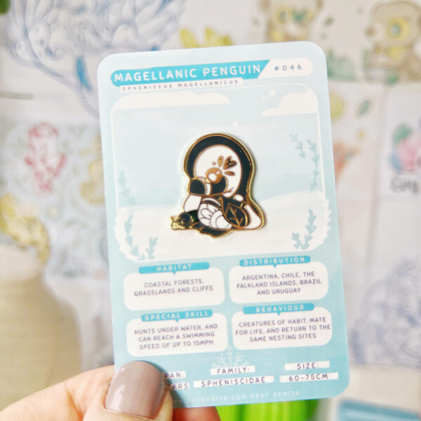 Magellanic Penguin hard enamel pin by Evy Benita. The pin is presented on a card decorated by species fun facts.