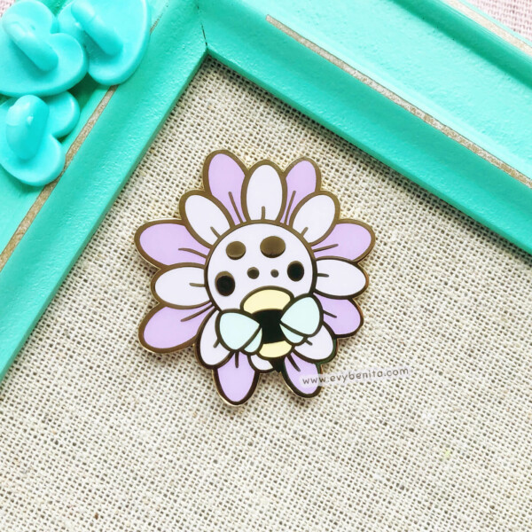 Cute lilac wildflower enamel pin with a small bee, illustrated in a cartoon style by Evy Benita