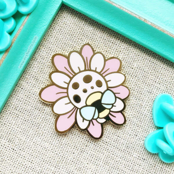 Cute pink wildflower enamel pin with a small bee, illustrated in a cartoon style by Evy Benita