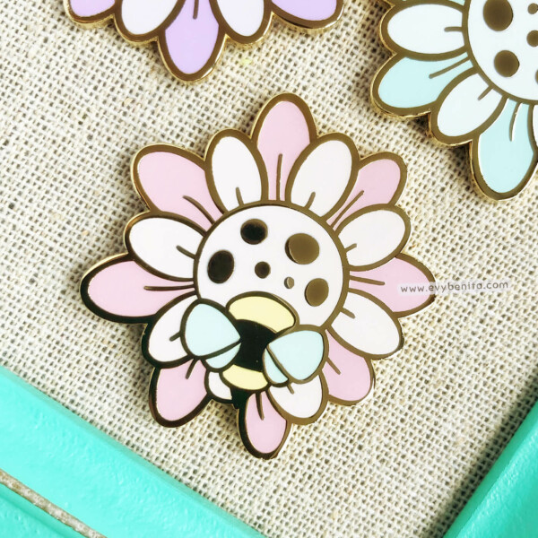Cute pastel wildflower enamel pin with a small bee, illustrated in a kawaii style by Evy Benita