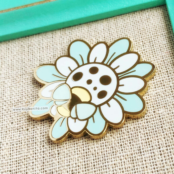 Cute baby blue wildflower enamel pin with a small bee, illustrated in a kawaii style by Evy Benita