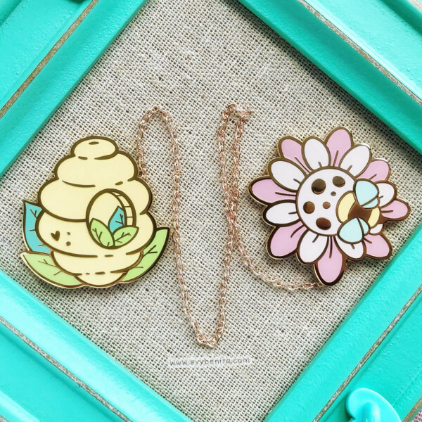 Cute kawaii enamel pin set of a bee hive and a wildflower bee. Both pins are held together by a detachable metal chain.
