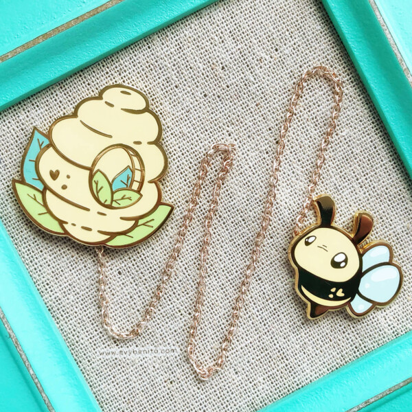 Cute kawaii enamel pin set of a bee hive and a bumblebee. Both pins are held together by a detachable metal chain.