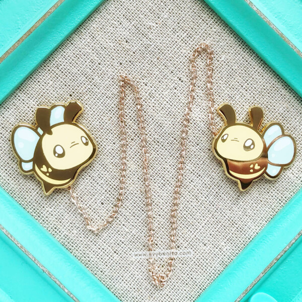 An adorable bumblebee enamel pin set featuring two enamel pins, each representing one cartoon-style bee, connected together by a detachable chain. The chain is approximately 11 inches long, so it works great as both a collar piece and as bag decor.