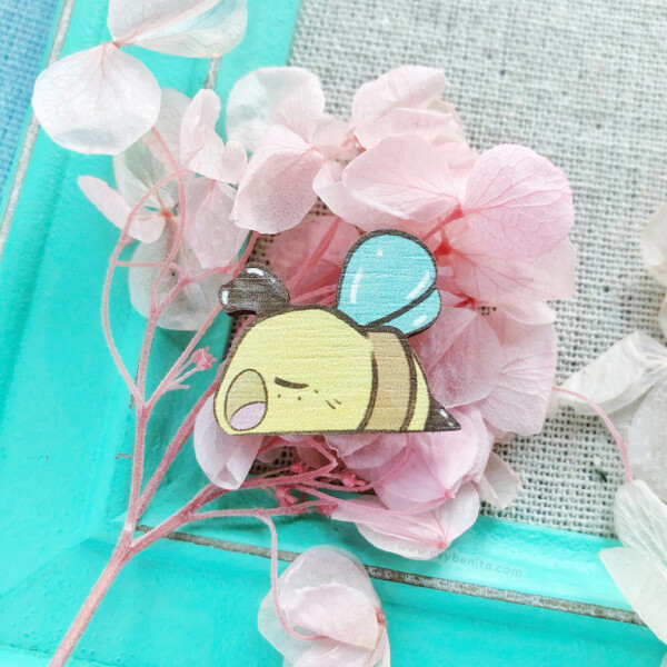 A sleepy bumble bee pin badge by Evy Benita. This bee pin is made with sustainably sourced European birch wood, and illustrated in a watercolor cartoon aesthetic.