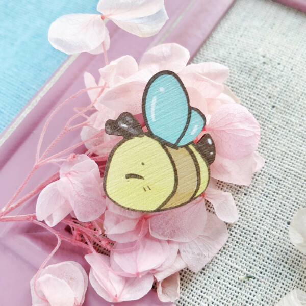 A happy bumble bee pin badge by Evy Benita. This bee pin is made with sustainably sourced European birch wood, and illustrated in a watercolor cartoon aesthetic.