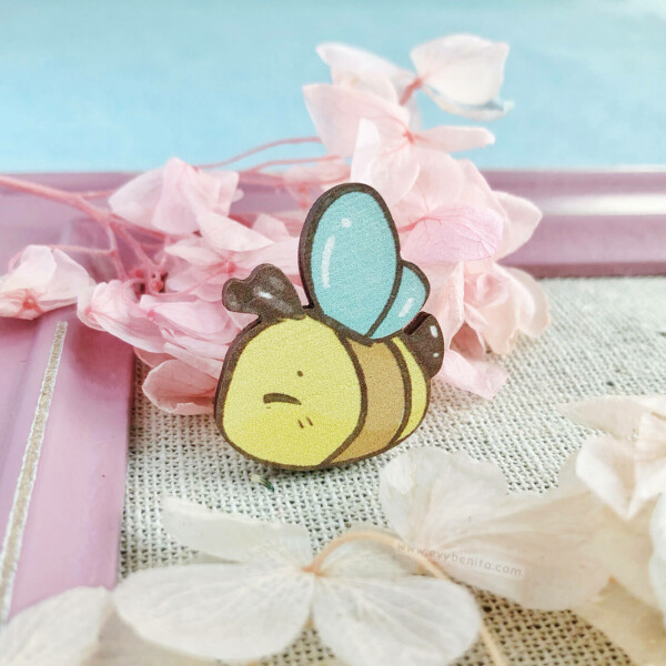 An adorable bumble bee pin badge by Evy Benita. This bee pin is made with sustainably sourced European birch wood, and illustrated in a watercolor cartoon aesthetic.