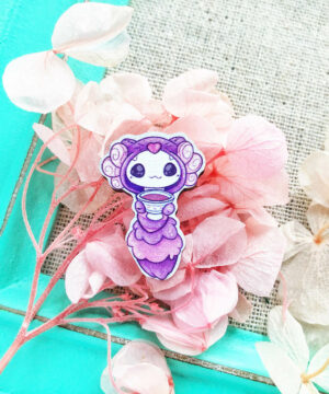 A cute miniature wooden pin featuring a kawaii axolotl dressed up as the Cheshire Cat from Alice in Wonderland. Illustrated by Evy Benita.
