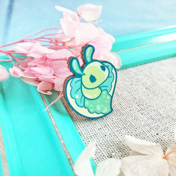 """Heart-shaped """"Emerald Elysia"""" sea slug wooden pin. Made in the UK and illustrated by Evy Benita."""