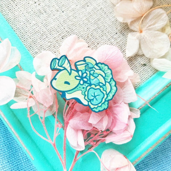 """Vibrant """"Elysia Crispata"""" sea slug wooden pin. This cute type of sea slug is often nicknamed the """"Lettuce"""" nudibranch. Made in the UK and illustrated by Evy Benita."""