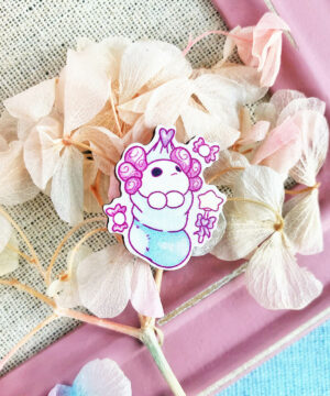 A wooden pin showing an axolotl sleeping in a fluffy Christmas stocking. Illustrated by Evy Benita.